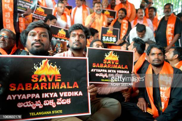 Members of the Sabarimala Ayyappa Seva Samajam pose with placards during a protest in Hyderabad on November 20 following the arrest of devotees at...