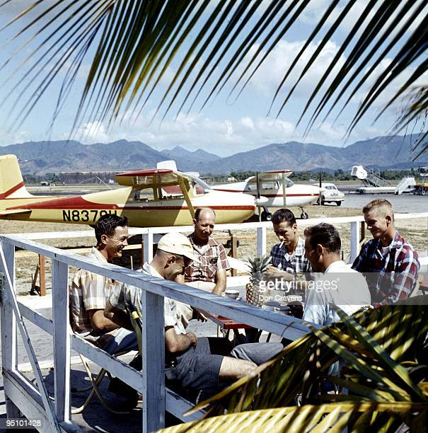 Members of the SAC aero club sit at an outdoor table, complete with a pineapple, near their parked planes during a Caribbean island hopping holiday,...