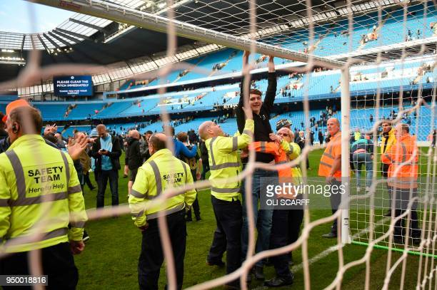 Members of the safety team try to clear a fan from the pitch during a pitch invasion at the end of the English Premier League football match between...