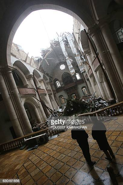 Members of the Saint Elias Cathedral committee inspect the damage inside east Aleppo's crumbling church in the Old City on December 21 2016 After...