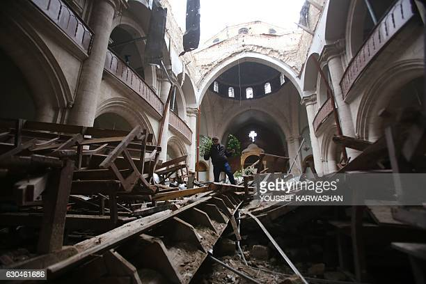 TOPSHOT Members of the Saint Elias Cathedral committee inspect the damage inside east Aleppo's crumbling church in the Old City on December 21 2016...