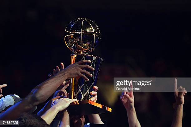Members of the San Antonio Spurs hold up the Larry O'Brien Championship Trophy after winnin Game Four of the NBA Finals against the Cleveland...