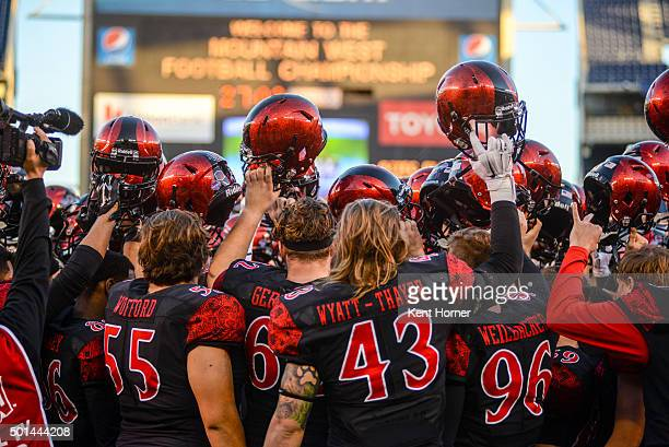 Members of the San Diego State Aztecs raise their helmets after practicing prior to playing the Mountain West Championship game against the Air Force...