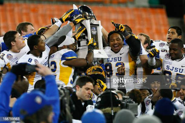 Members of the San Jose State Spartans hold up the trophy after defeating the Bowling Green Falcons 29-20 to win the Military Bowl at RFK Stadium on...