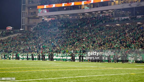 Members of the Saskatchewan Roughriders link arms during the national anthem in a show of unity with NFL players before the game between the Ottawa...