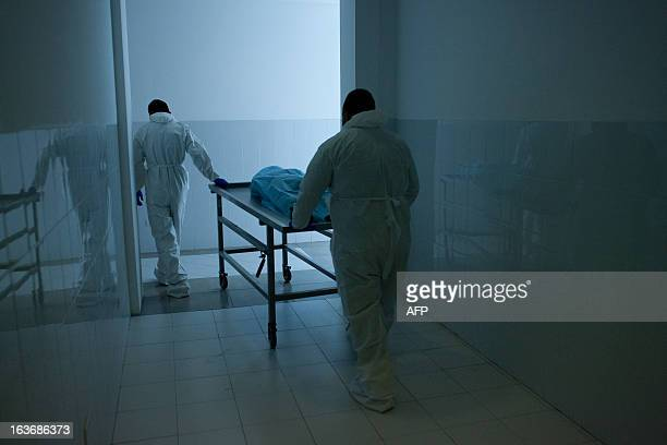 Members of the scientific team of Mexican dentist Alejandro Hernandez Cardenas carry a gurney with mummified human corpse to rehydrate it in a...