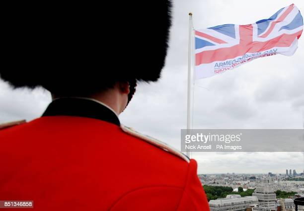 Members of the Scots and Coldstream Guards stand on the roof of Westminster City Hall Westminster central London as the Armed Forces flag is raised...