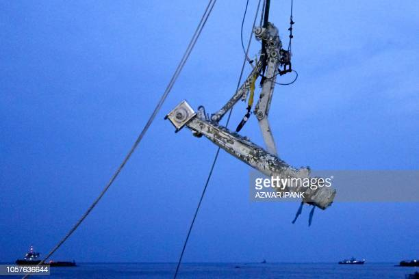 Members of the search team lift part of the landing gear of the illfated Lion Air flight JT 610 during search operations at sea off the coast from...
