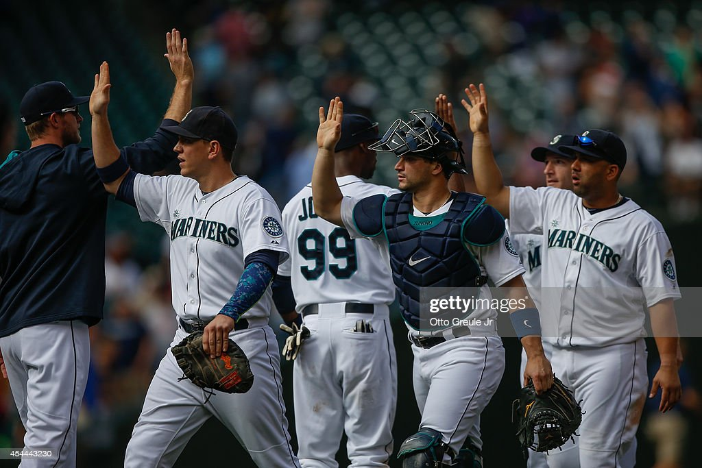 Members of the Seattle Mariners celebrate after defeating the Washington Nationals 5-3 at Safeco Field on August 31, 2014 in Seattle, Washington.