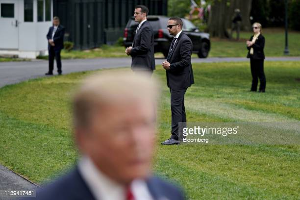 Members of the Secret Service stand past US President Donald Trump left on the South Lawn of the White House in Washington DC US on Friday April 26...