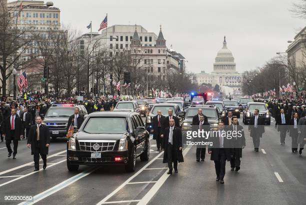 Members of the secret service walk next to the limousine carrying US President Donald Trump and First Lady Melania Trump drives in the 58th...