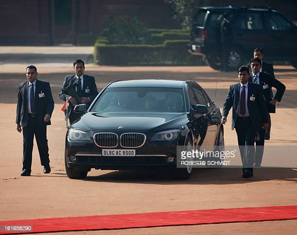 Members of the security detail of Indian Prime Minister Manmohan Singh flank his vehicle moments after the dignitary's arrival at the Presidential...