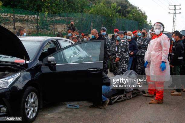 Members of the security forces gather as medics evacuate the body of prominent Lebanese activist and intellectual Lokman Slim from the spot where he...