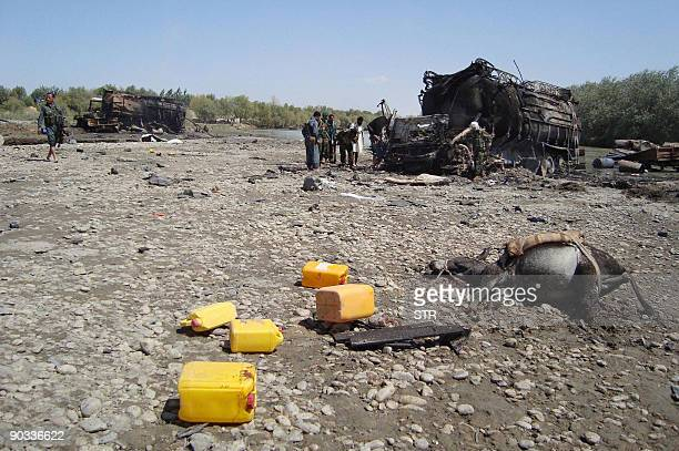 Members of the security forces walk at the site of a NATO airstrike which destroyed two fuel tankers hijacked by the Taliban in northern Kunduz on...