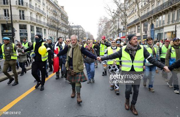 Members of the security team of the gilets jaunes movement wearing a white armband hold hands as they lead an antigovernment demonstration march...