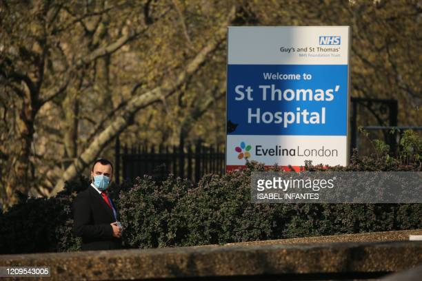 Members of the security team wearing a mask as a precaution stands by a sign outside St Thomas' Hospital in central London on April 9 where Britain's...