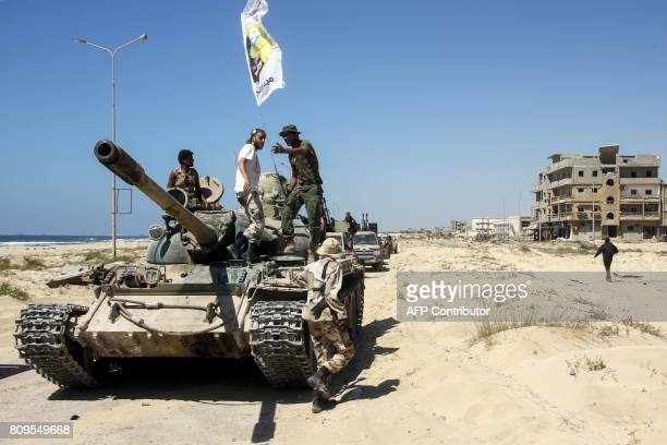 TOPSHOT Members of the selfstyled Libyan National Army loyal to the country's east strongman Khalifa Haftar ride over a tank in the eastern city of...