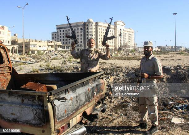 Members of the selfstyled Libyan National Army loyal to the country's east strongman Khalifa Haftar holds up two Kalashnikov assault rifles as he...