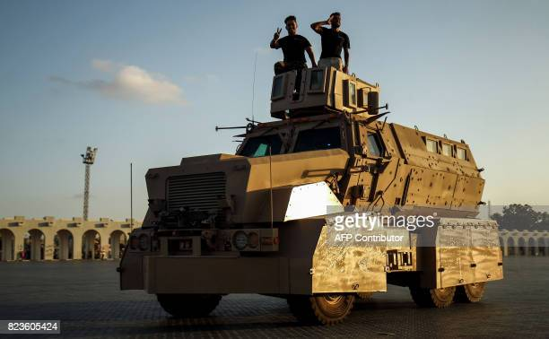 Members of the selfstyled Libyan National Army loyal to the country's east strongman Khalifa Haftar flash the victory gesture from atop an armoured...
