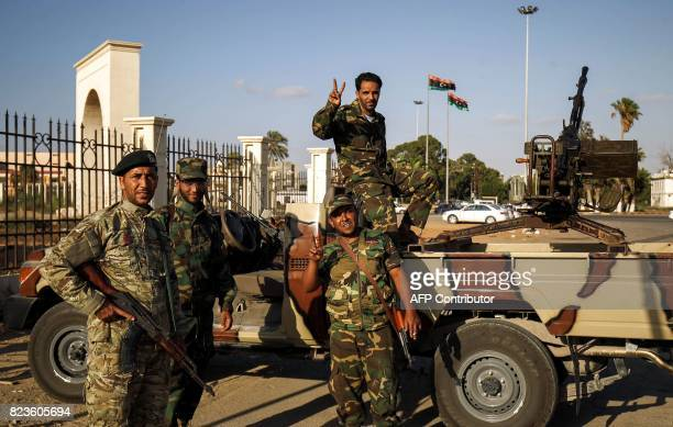 Members of the selfstyled Libyan National Army loyal to the country's east strongman Khalifa Haftar flash the victory gesture next to a...