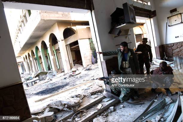 Members of the selfstyled Libyan National Army loyal to the country's east strongman Khalifa Haftar take cover as they open fire during clashes with...