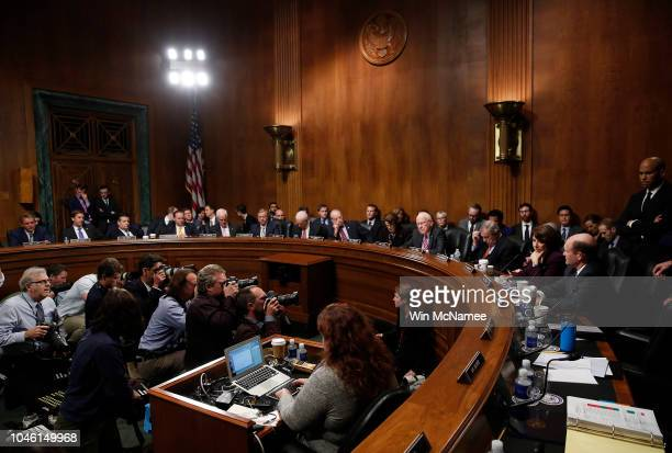 Members of the Senate Judiciary Committee listen as Sen Jeff Flake speaks with Sen Chris Coons after Flake announced he is in favor of additional...