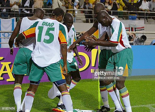 Members of the Senegal team celebrate after scoring over France in the opening match of the 2002 FIFA World Cup Korea/Japan tournament in Seoul 31...