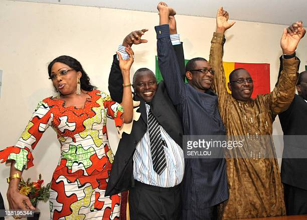 Members of the Senegalese opposition Diouma Dieng Diakhate Alioune Tine Youssou Ndour and Macky Sall raise their hands together during a press...
