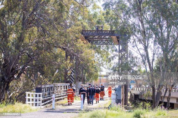 Members of the SES and NSW Health walk across the Wilcannia Bridge over the Darling-Baaka River on September 06, 2021 in Wilcannia, Australia. Thirty...