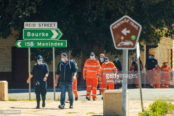 Members of the SES and NSW Health walk through the main street on September 06, 2021 in Wilcannia, Australia. Thirty motorhomes have been set up in...