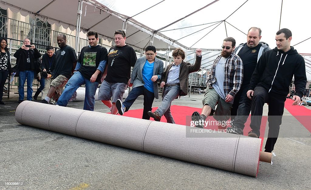 Members of the setup crew are joined by actors Rico Rodriguez (4th L) and Nolan Gould (4th R) while rolling out the red carpet in Los Angeles on January 26, 2013 during preparations ahead of the 19th Annual Screen Actors Guild (SAG) Awards on January 27. AFP PHOTO/Frederic J. BROWN