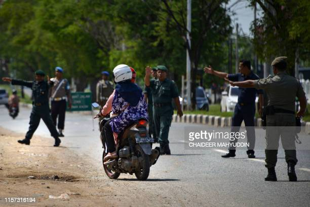Members of the Sharia police stop passing motorists for a Shariacompliant dress code check along a road in Lambaro Aceh province on July 23 2019 Aceh...