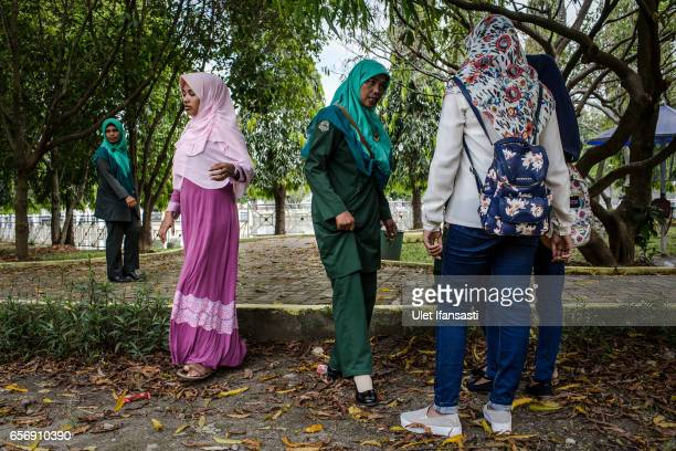 Members of the sharia police women known as Wilayatul Hisbah stop teenage girls who are wearing tights which goes against the prevailing sharia law...