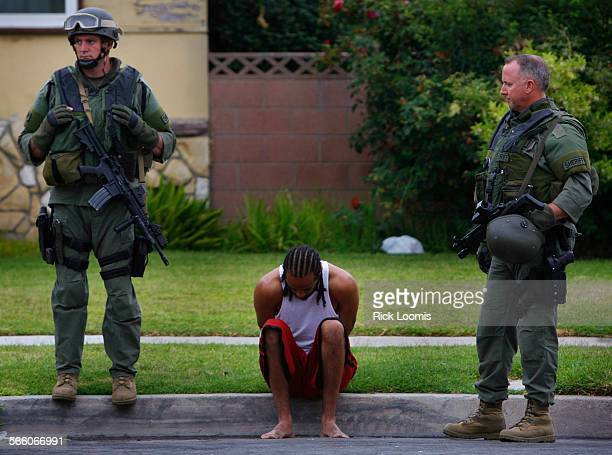 Members of the Sheriff's Dept watch over an man detained during a gang sweep conducted on Tuesday July 8 2008 throughout several areas in Los Angeles...