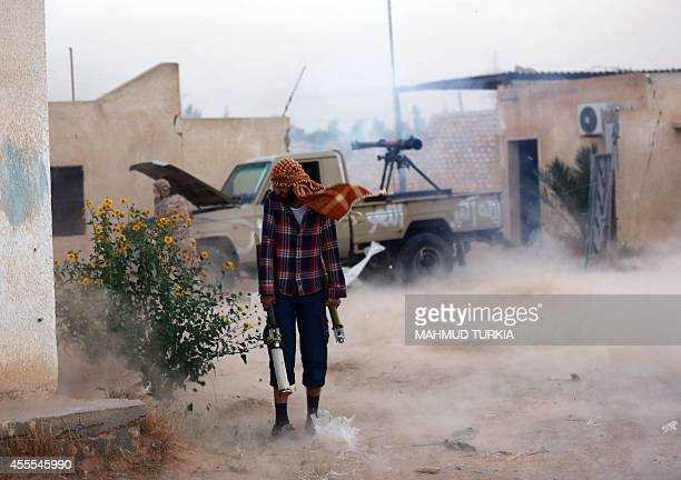 Members of the Shield Brigade backed by some local fighters from the western region fire an antitank cannon mounted on a pickup truck during clashes...