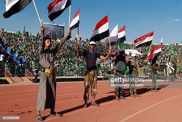 Members of the Shiite Huthi rebels wave the Yemeni flag as they stand guard as Yemeni Muslims take part in a rally on the eve of the anniversary of...