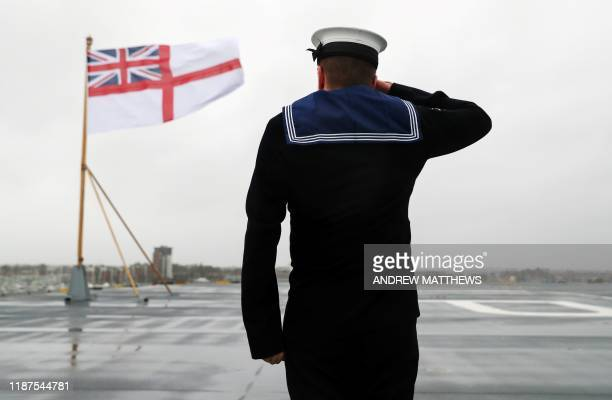 Members of the ship's company raise the White Ensign on the stern of the Royal Navy aircraft carrier HMS Prince of Wales during her commissioning...