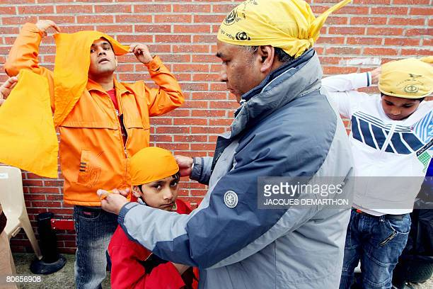 Members of the Sikh community adjust their turban during their Baisakhi celebrations in Bobigny suburb of Paris on April 13 2008 Hundred of French...