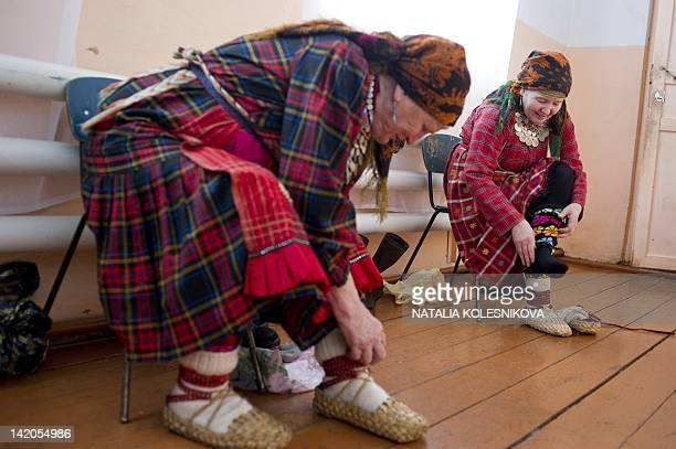Members of the singing group Buranovskiye Babushki put on their bast shoes as they prepare for a rehearsal at the local club in the village of...