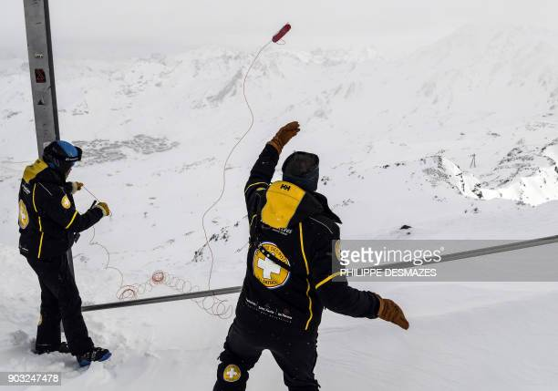 Members of the ski patrol and bomb expert throws a 25 kg dynamite stick prior to blast it as part of avalanche maintenance on January 10 2018 in Val...