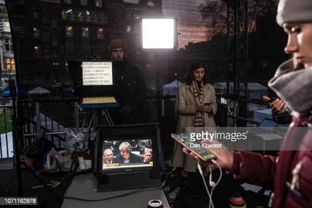 Members of the SKY news team relax in a make shift studio on Abingdon Green as a screen showing British Prime Minister Theresa May speaking in the...