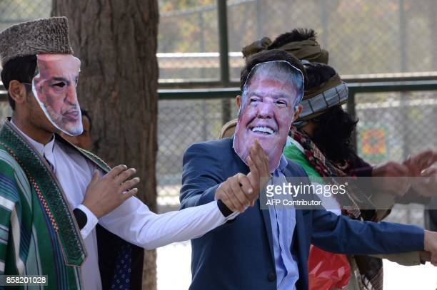 Members of the Solidarity Party of Afghanistan stage a satirical protest show including actors wearing a mask of US President Donald Trump and former...