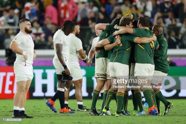 Members of the South Africa team celebrate victory as Luke CowanDickie and and Maro Itoje of England look on dejected during the Rugby World Cup 2019...