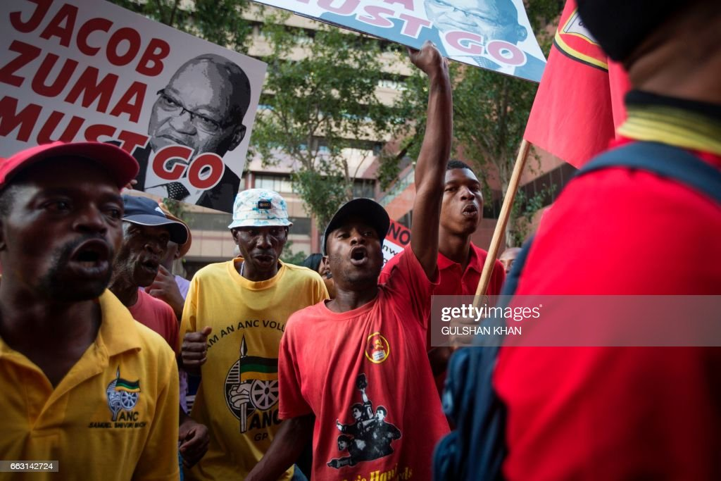 Members of the South African Communist Party (SACP) and attendees of the Memorial of the late anti-apartheid activist Ahmed Kathrada protest outside the Johannesburg City Hall as they call for President of South Africa Jacob Zuma to step down on April 1, 2017 in Johannesburg. The Ahmed Kathrada Foundation holds a memorial service for the anti-apartheid stalwart, after the government called off a planned event to commemorate him. The event comes days after President Jacob Zuma's shock sacking of finance minister Pravin Gordhan in a cabinet purge that has plunged the ruling ANC into chaos. /