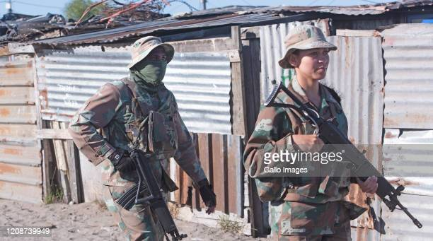 Members of the South African National Defence Force , the Police Gang Unit and Metro Police patrol the streets of Lavender Hill and Hillview warning...