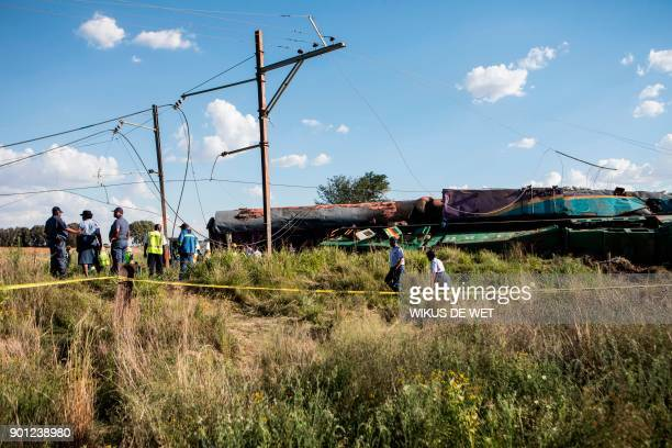 Members of the South African Police Service and Passenger Rail Agency South Africa look at a derailed train locomotive after an accident near...