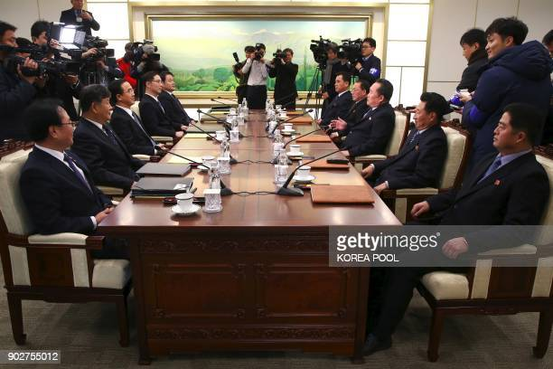 Members of the South Korea delegation talk with members of the North Korean delegation during their meeting at the border truce village of Panmunjom...