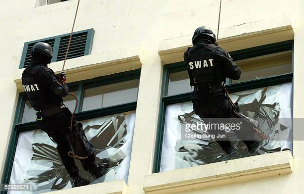 Members of the South Korean Special Weapons and Tactics team rappel down a wall during anti-terrorism exercises at a training camp on May 30, 2005 in...