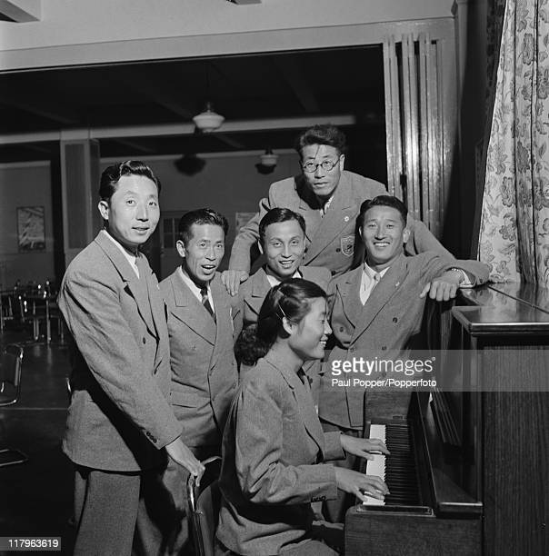 Members of the South Korean team around a piano at an Olympic village, during the London Olympics, 1948. At the piano is the team's only female...