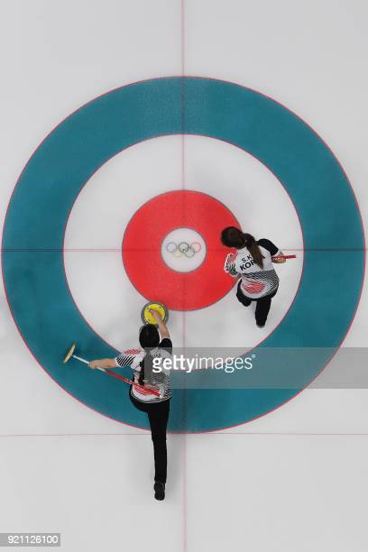 TOPSHOT Members of the South Koren team play a shot during the curling women's round robin session between the US and South Korea during the...